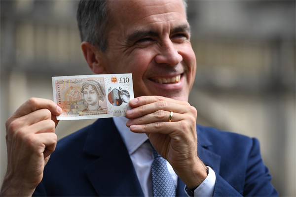 ​Bank of England Governor Mark Carney shows a ten pound note featuring author Jane Austen, during its unveiling at Winchester Cathedral on July 18, 2017 in Winchester, England. ​